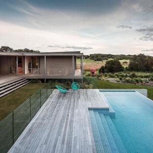 Ispirazione per una grande piscina a sfioro infinito minimal personalizzata con pedane