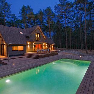 Aménagement d'une grande piscine sur une terrasse en bois arrière contemporaine rectangle.