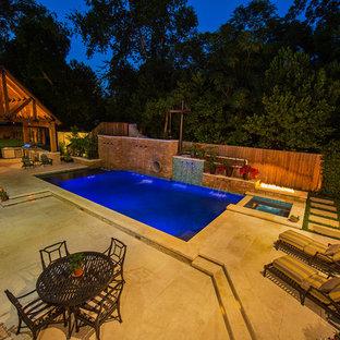 Diseño de piscina con tobogán alargada, de estilo de casa de campo, grande, rectangular, en patio lateral, con adoquines de piedra natural