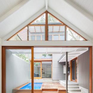 Ejemplo de piscina alargada, escandinava, de tamaño medio, en patio, con entablado