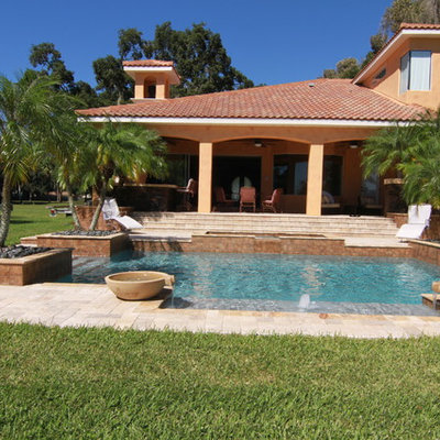 Example of a mid-sized tuscan backyard stone and rectangular lap pool fountain design in Tampa