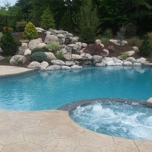 Modelo de piscinas y jacuzzis naturales, vintage, extra grandes, redondeados, en patio trasero, con suelo de hormigón estampado