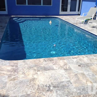 Inspiration for a large modern backyard stone and rectangular aboveground pool remodel in Miami