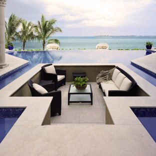 Diseño de piscina infinita, tradicional, extra grande, a medida, en patio trasero, con suelo de baldosas