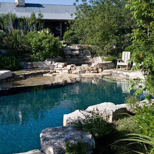 Hot tub - mid-sized farmhouse backyard stone and custom-shaped natural hot tub idea in Austin