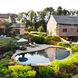 Modelo de casa de la piscina y piscina natural, rústica, de tamaño medio, tipo riñón, en patio trasero, con adoquines de piedra natural