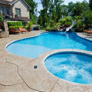 Foto de piscina con tobogán contemporánea, grande, a medida, en patio trasero, con suelo de hormigón estampado
