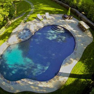 Imagen de piscina natural, rural, de tamaño medio, a medida, en patio trasero, con losas de hormigón