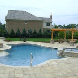 Imagen de piscinas y jacuzzis naturales, tradicionales, de tamaño medio, a medida, en patio trasero, con adoquines de hormigón