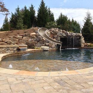 Exemple d'une grande piscine naturelle et arrière craftsman sur mesure avec un toboggan et des pavés en béton.