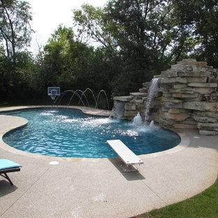 Idée de décoration pour une piscine arrière design de taille moyenne et sur mesure avec un toboggan et du béton estampé.