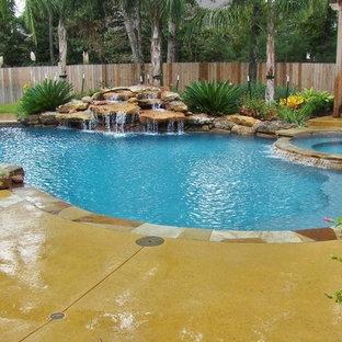 Diseño de piscina con fuente moderna, grande, a medida, en patio trasero, con suelo de hormigón estampado