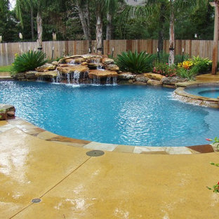 Photo of a large modern backyard custom-shaped pool in Houston with a water feature and stamped concrete.