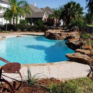 Diseño de piscina tradicional renovada, a medida, en patio trasero, con granito descompuesto