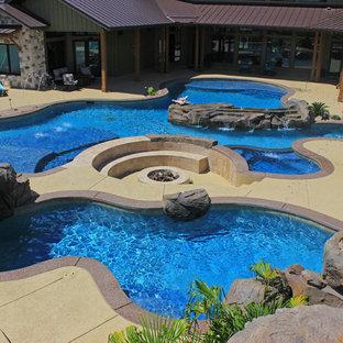 Ispirazione per un'ampia piscina naturale stile marinaro personalizzata dietro casa con un acquascivolo e pedane