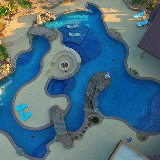 Foto di un'ampia piscina naturale stile marinaro personalizzata dietro casa con un acquascivolo e pedane