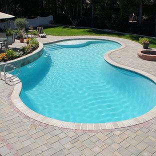 Imagen de piscina con fuente natural, clásica, de tamaño medio, tipo riñón, en patio trasero, con adoquines de hormigón