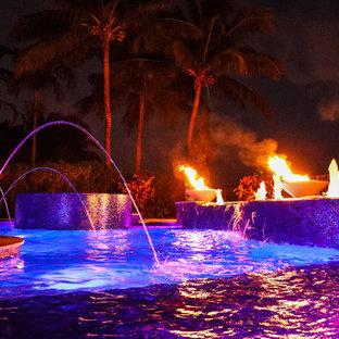 マイアミの大きいオーダーメイドトロピカルスタイルのおしゃれなプール (天然石敷き) の写真