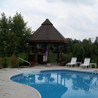 Imagen de piscina con fuente natural, de estilo americano, grande, a medida, en patio lateral, con adoquines de piedra natural