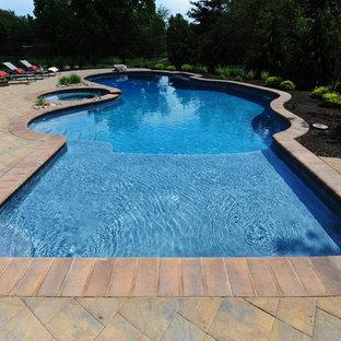 Diseño de piscina con fuente clásica, de tamaño medio, a medida, en patio trasero, con adoquines de hormigón