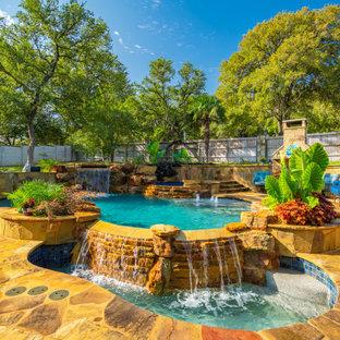 Ispirazione per una grande piscina naturale tropicale personalizzata dietro casa con pedane