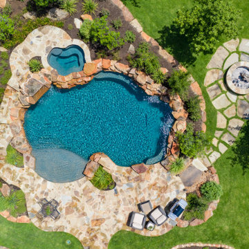 Freeform pool with weeping wall, grotto, and spa in San Antonio, Tx