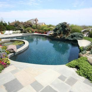 Ejemplo de piscina natural, marinera, grande, tipo riñón, en patio trasero, con adoquines de piedra natural