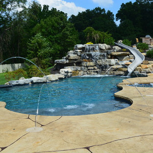 Imagen de piscina con tobogán actual, grande, a medida, en patio trasero, con suelo de hormigón estampado