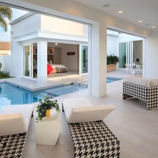 Modelo de piscina con fuente moderna, en forma de L, en patio, con suelo de baldosas