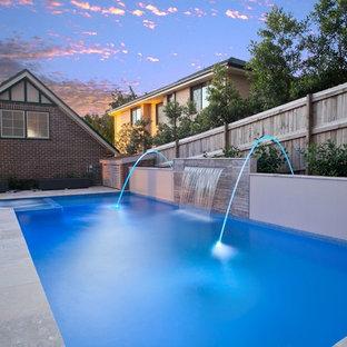 Imagen de piscina con fuente actual, de tamaño medio, rectangular, en patio trasero