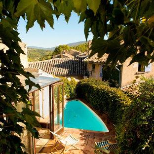 Aménagement d'une petit piscine méditerranéenne sur mesure avec une cour et du carrelage.