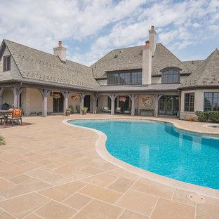 Foto de piscinas y jacuzzis rústicos, de tamaño medio, a medida, en patio trasero, con adoquines de hormigón