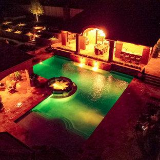 """Idee per una piscina monocorsia classica a """"L"""" di medie dimensioni e dietro casa con una dépendance a bordo piscina e pavimentazioni in pietra naturale"""