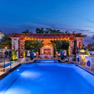 Пример оригинального дизайна интерьера: огромный прямоугольный бассейн-инфинити на заднем дворе в средиземноморском стиле с джакузи и покрытием из плитки