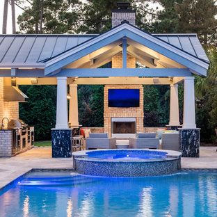 Large traditional rectangular swimming pool in Other with a pool house and concrete paving.