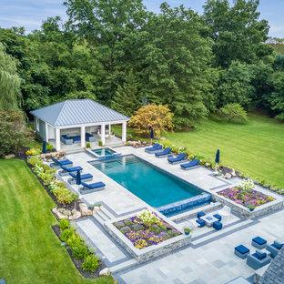Großer Klassischer Infinity-Pool hinter dem Haus in rechteckiger Form mit Poolhaus und Natursteinplatten in New York