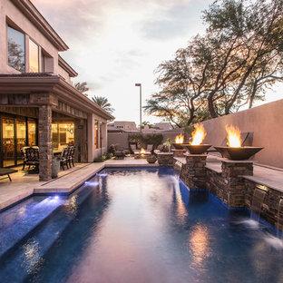 Diseño de piscina con fuente tradicional renovada, de tamaño medio, en forma de L, en patio trasero, con adoquines de piedra natural