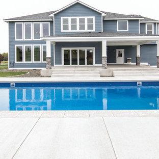 Foto de piscina alargada, de estilo americano, grande, rectangular, en patio trasero, con losas de hormigón