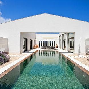 Diseño de piscina alargada, contemporánea, extra grande, rectangular, en patio, con gravilla