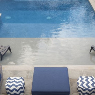 Large contemporary side yard rectangular pool in Toronto with a water slide and natural stone pavers.