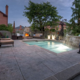Example of a small trendy backyard stamped concrete and custom-shaped hot tub design in Toronto