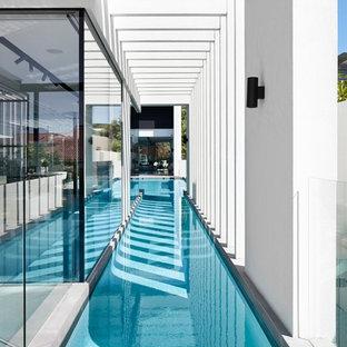 """Esempio di una grande piscina monocorsia minimal a """"L"""" in cortile"""
