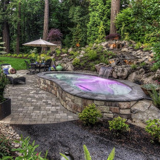 Design ideas for a small transitional backyard kidney-shaped aboveground pool in Orange County with a water feature and natural stone pavers.