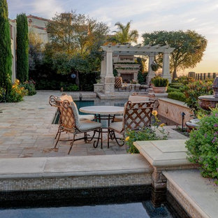 Photo of a medium sized mediterranean back custom shaped lengths swimming pool in Orange County with a hot tub and natural stone paving.