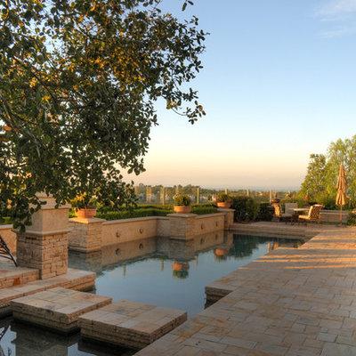 Mid-sized tuscan backyard tile and custom-shaped lap pool photo in Orange County