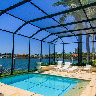 Imagen de casa de la piscina y piscina tropical, grande, a medida y interior, con adoquines de ladrillo