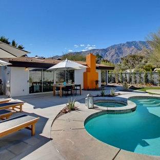 Diseño de piscinas y jacuzzis retro, de tamaño medio, tipo riñón, en patio trasero, con adoquines de hormigón