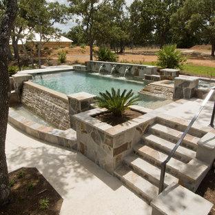 Foto de piscina con fuente infinita, mediterránea, de tamaño medio, a medida, en patio trasero, con adoquines de hormigón