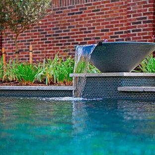 Diseño de piscina con fuente actual, de tamaño medio, rectangular, en patio trasero, con losas de hormigón