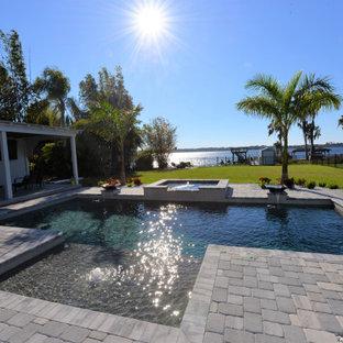 Foto de piscina clásica, grande, rectangular, en patio trasero, con adoquines de ladrillo